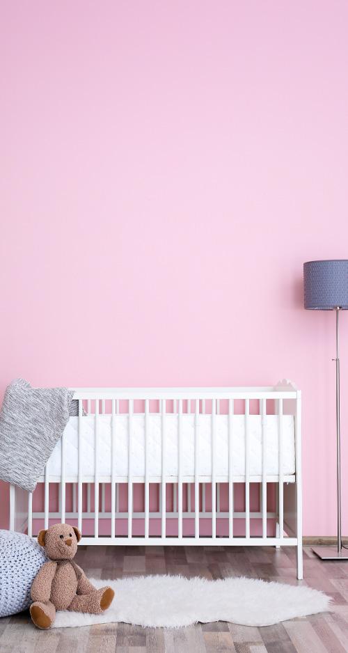 babyhuis bedje tegen een roze muur